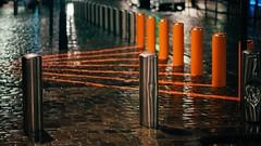 Lifelines (Tom Levold (www.levold.de/photosphere)) Tags: brussels bruxelles brüssel fujixpro2 xf56mmf12 street ig night nacht regen rain spiegelung reflection copplestones pflaster still stillleben orange bollards poller