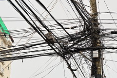 Wire tangle on electric pole. Street of downtown Dumaguete-Philippines. 0521 (rweisswald) Tags: house building edifice electricpole utilitypole powerline publicutility electricity mains gridcircuit electricwire electricalcable electriccurrent distribution voltage electricline powersupply tangle mess jam thicket entanglement confusion skein muddle turmoil clutter chaos ugly ugliness corner facade beigewall windowrow greenplastic canopy awning curl loop transmissiontower powertower electricitypylon latticetower transformer wood overheadcable dumaguete negrosoriental centralvisayas philippines