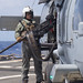 Holds a .50 caliber machine gun outside of an SH-60S Seahawk while operating in the Philippine Sea