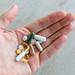 Hand hält verschiedene Tabletten und Vitaminpillen vor grauem Hintergrund