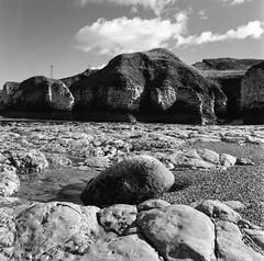 Selwicks Bay (Richie Rue) Tags: beach eastcoast stones rocks cliffs cloud monochrome blackandwhite bnw 120 mediumformat squareformat 6x6 film analogue foma fomafomapan100 champion promicrol mamiya c220 tlr ishootfilm istillshootfilm filmsnotdead landscape outdoors fineart filmdev:recipe=11833 film:brand=foma film:name=fomafomapan100 film:iso=100