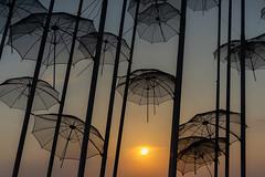 "Sunset through the Umbrellas (George Tzanis) Tags: umbrellas sun sunset night architecture sculpture thessaloniki zongolopoulos greece sky dark light sony a7ii ilce7m2 urban city 1997 art sea coast beach ""canon fd 50mm f14"" macedonia θεσσαλονίκη μακεδονία"