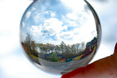 Looking Through A Lensball. (dccradio) Tags: lumberton nc northcarolina robesoncounty outside outdoor outdoors lensball lensballphotography tensphy sky clouds bluesky march spring springtime nature natural landscape hand finger thumb nikon d40 dslr crystalball glassball glass circle round saturday weekend saturdayafternoon afternoon goodafternoon dumpster trashbin redtruck truck pickup pickuptruck tree trees woods wooded forest parking parkinglot paved pavement