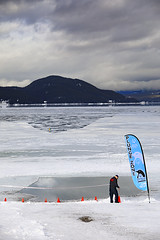 The Plunge Is Done (Till Next Year) (wyojones) Tags: montana whitefish whitefishlake citybeach lowclouds clouds ice winter trees slopes mountain shoreline feburary snow man fireman holeinice water spenquinplunge banner flag rope ropingoff orangecones reflection cloudscape
