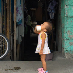 Oops (Beegee49) Tags: street child drinking baby cup playing happy planet luminar sony a6000 bacolod city philippines asia happyplanet asiafavorites