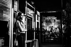Recharging (Kieron Ellis) Tags: woman phone busstop waiting energy sunny bright shadow contrast candid street blackandwhite blackwhite monochrome