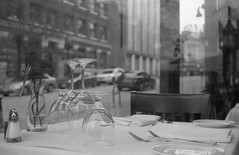 table for two (Yutaka Seki) Tags: konicaautos2 kentmere400 blackandwhite film analogue grainy table glasses forks window restaurant