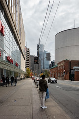 Waiting for His Bus (Jocey K) Tags: sonydscrx100m6 triptocanada ontario canada autumn toronto city streets people highrise clouds sky buildings architecture cars signs signage trees