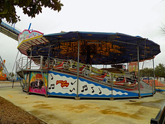 American Swing Carnival Ride. (dccradio) Tags: myrtlebeach sc southcarolina horrycounty outside outdoor outdoors americanswing bertazzon swingbuggy musicride himalaya flyingbobs thunderbolt rail railing tub tubs carnival midway fairride amusements amusementdevice mechanicalride ride rides thrillride outdooramusement fun entertainment color colorful nikon coolpix l340 bridgecamera broadwayatthebeach amusementpark pavilionamusementparkcentral pavilionparkcentral pavilionamusementpark pavilionpark tree treebranch branch branches cement grass ground browngrass car oldcar lights musicalnotes notes music words text