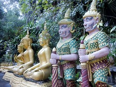 Feminine Buddha with Costumed Friends (mikecogh) Tags: luangprabang statues buddha feminine figures costume breasts culture