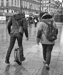 Your Supposed To Use Both Feet (tcees) Tags: garedunord ruededunkerque paris x100 fujifilm finepix urban streetphotography street pavement sidewalk bw mono monochrome blackandwhite france man woman people statue rain umbrella lamppost shops building balcony wet reflection