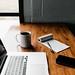 MacBook Pro, white ceramic mug,and black smartphone on table - Credit to https://myfriendscoffee.com/
