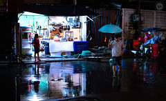 Aqua Night (dlerps) Tags: bkk bangkok city daniellerps lerps sony sonyalpha sonyalpha99ii tha thai thailand urban lerpsphotography metropolitan umbrella puddle water reflection rain man male shop store light night evening sukhumvitsoi57 wet wetseason street asia asian streetphotography grocery carlzeiss planart1450 carlzeissplanar50mmf14ssm flodded aqua turquoise happyplanet asiafavorites