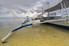 Deck of balangay or bangka boat stranded on Punta Ballo beach-Sipalay-Philippines.0345 (rweisswald) Tags: beach seaside shore lowtide shallowwater boat ship vessel watercraft banca bangka paraw outrigger balangay touristboat blue white deck woodplank woodenbench ladder walkway bamboomast greennet blacknet helm bow port starboard stern fabric canvasawning sunshade canopy beached stranded moored yellowrope cord knot tied cloudy overcast diving snorkeling puntaballo sipalay negrosoccidental westernvisayas philippines