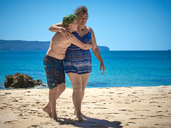 Otama February 228 (ArdieBeaPhotography) Tags: beach ocean shore coast sunny summer day hot warm holiday preteen woman mother son boy green hair embrace cuddle hold hug walk wife swimsuit togs onepiece