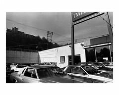 Car lot (Richard C. Johnson: AKA fishwrapcomix) Tags: leicam2 leitzelmar50mmf28 film kodaktx analog analogue scanfromnegative filmisnotdead iusedtoshootfilm istillshootfilm blackandwhite bw monochrome building 1980s archive automobiles parkinglot utilitypoles mybackpages iwassomucholderthan outdoor
