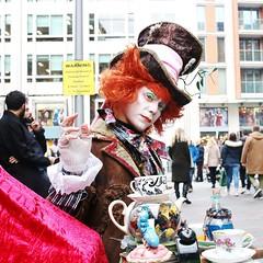 WARNING: Tea Party in progress.... (markwilkins64) Tags: london knightsbridge streetphotography street streetportrait portraiture portrait hat madhatter lipstick mistletoe orange warning markwilkins teapot alarmclock potion stare makeup teacups