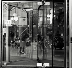 Revolving Doors (Bury Gardener) Tags: burystedmunds bw blackandwhite britain monochrome mono england eastanglia uk people peoplewatching folks nikond7200 nikon suffolk streetphotography street streetcandids snaps strangers candid candids arc thearc