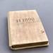Gästebuch mit Holzcover des Hotel 1898 auf der La Rambla in Barcelona auf grauem Untergrund
