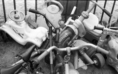 Pileup (Arne Kuilman) Tags: amsterdam nikonf 50mmf2 nikkorhc slr apx400 agfa id11 10minutes homedeveloped nederland kinderfietsen childrensbikes bikes toys speelplaats