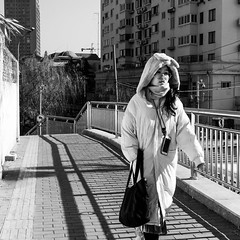 Bunny (Go-tea 郭天) Tags: qingdao shandong républiquepopulairedechine cn bunny rabbit coat cold winter sun sunny shadow young lady woman portrait alone lonely walking walk purse bag glasses mobile phone cellular cellphone scarf hood ears street urban city outside outdoor people candid bw bnw black white blackwhite blackandwhite monochrome naturallight natural light asia asian china chinese canon eos 100d 24mm prime cute