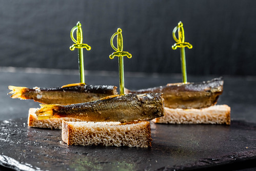 Sprat canape with brown bread on black background