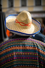 Person with Mexican poncho and sombrero