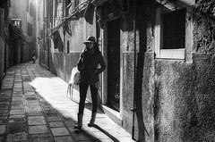 Canareggio side street. (markfly1) Tags: woman walking panama hat elegant stylish tall brigh ligh dark shadow boots black white candid image highlights shadows monochrome baw bw light leak kodak trix 400 pushed film underexposed canareggio venice italy europe analogue analog street photo pedestrain pavement lines windows doors nikon fm3a 35mm manual focus lens filmnotdead