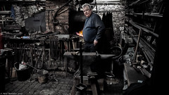 The smith, a mighty man. (Neil. Moralee) Tags: branscombeforgeneilmoralee neilmoralee colour blacksmith forge iron steel metal smith smithy village portrait face man mature old skill craft kraft craftsman work working master neil moralee olympus hammer anvil power fire flame coal strike