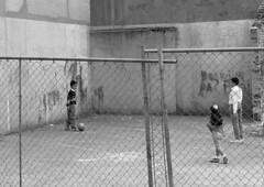 Practice with football (rob kraay) Tags: football ironfence blackandwhite robkraay concretewalls urbanrenewal netting people demolishedhouses graffiti cityrenovation bw