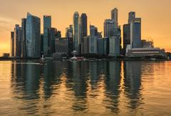 Golden Marina Bay (henriksundholm.com) Tags: marinabay singapore skyline city cityscape landscape river ripples reflections skyscraper hdr fullertonhotel maybanktower boat southeast asia sunset golden