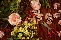 Wrapped in a Wreath (flashfix) Tags: april062019 2019inphotos flashfix flashfixphotography ottawa ontario canada nikond7100 28mm stilllife feelingcraft dim diy flowers floral scissors pliers table wreath twigs leaves floralarrangement flatlay lines textures pink yellow green spring craft