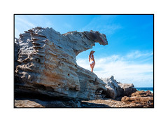 Woman standing in a sandstone formation by the ocean (sugarbellaleah) Tags: woman bikini summer holiday vacation nature rock formation weathered eroded geology sandstone patterns texture people leisure recreation outdoors swimsuit looking suntan australia travel tourism background copyspace legs standing sunhat summertime season landscape sky arched crumbling lifestyle culture fit australianculture aussie adult jervisbay