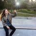 Girl Pointing Upwards towards a Light at a Skate Park while Sitting