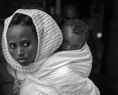 Children feel secure and are not traumatized, as much as their parents feel secure, more than anything else (ybiberman) Tags: israel jerusalem ethiopianchurch ethiopiancathedral boy mother veil portrait candid streetphotography bw people carry eyecontact hairdo