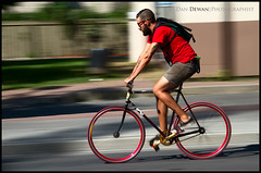 Red Wheels on Bank Street (Dan Dewan) Tags: centretown dandewan bicycle bankstreet people canon 2013 red colour portrait ottawacyclist cyclist ottawa motion man ontario pan canonefs18135mmf3556is august colourful canada glasses male canoneos7d bike