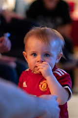 Baby look with piercing eyes (iamthecandleman) Tags: portrait baby todler eyes look stare manchester united football strip chew hand sony alpha ar2 irish