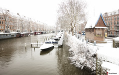 Amsterdam. (alamsterdam) Tags: amsterdam winter snow nassaukade canal houseboats boats cars people tram houses marnixkade kiosk