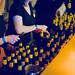 Lady bartenders opening huge amounts of beer bottles