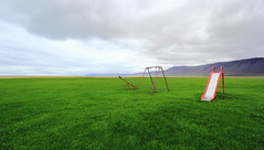 Empty Nest for Kids (Eye of Brice Retailleau) Tags: angle beauty composition landscape outdoor paysage perspective scenery scenic view extérieur cloud clouds cloudy cloudscape nuages backback backpacking travel traveling sky skyscape outside outdoors ciel panorama sea ocean seaside oceanside coast light europe arctic iceland islande beach plage playa patreksfjörður raudasandur melanes icelandic islandais color colour colors colours colorful colourful green grass playground slide toboggan swing balancoire