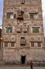 House Face, Sana'a (Rod Waddington) Tags: middle east yemen yemeni sanaa city unesco towerhouses tower house home boy culture cultural child architecture traditional tribe tribal windows door stone building