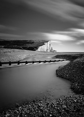 Haven Brow (Lloyd Austin) Tags: composition morning motion serene exposed ethereal atmospheric tranquil nationaltrust nationalpark nature havenbrow cuckmerehaven eastsussex england unitedkingdom gb uk sevensisters chalkcliffs coastline coastal coast sea seascape seaside seafront water ocean stones pebbles groyne river outflow cuckmere clouds cloudscape landscape light cliffs rocks beach sand outside lowtide tidal contrast tones white grey black mono monochrome bw bnw blackwhite dramatic vista view march majestic proud longexposure slowexposure slow filters stacking patience moody sigma1750mm shoreline ndfilter 3lt cablerelease nikond7200