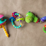 Plastic toys for newborn baby. Rattles on the paper background. Top view. thumbnail