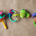 Plastic toys for newborn baby. Rattles on the paper background. Top view.