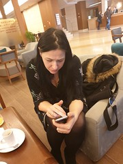 Zagreb - Coffee call (sean and nina) Tags: nina hotel zagreb january 2019 coffee seat seated sit sitting dress tights nylons shoes bare arms skin face candid mobile phone expression long dark hair brunette legs knees lobby loungs espresso expresso juice beauty beautiful gorgeous stunning charm charming cute woman female girl lady girlfriend fiancee wife married serb croatia hrvatska chair table