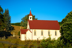 NZ Travels  - Pauatahanui Inlet 09 (ArdieBeaPhotography) Tags: village church wooden corrugatedironroof red painted graveyard building worship reverence cemetary gravestone grave hills rural trees belltower fence rail post small cross christian arched windows typical old clear blue sky