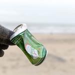 Hand in Handschuh hebt achtlos weggeworfene Bierdose vom Sandstrand auf thumbnail