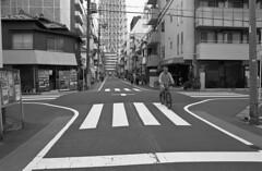 Man riding a bike (Manuel Goncalves) Tags: bike japan tokyo nikonn90s nikkor28mm kodaktmax400 blackandwhite 35mmfilm analogue urban street