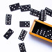 Top view of black and white domino set with wooden box on white background