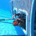 A Marine exits the side of a submerged helicopter during underwater egress training at Camp Hansen